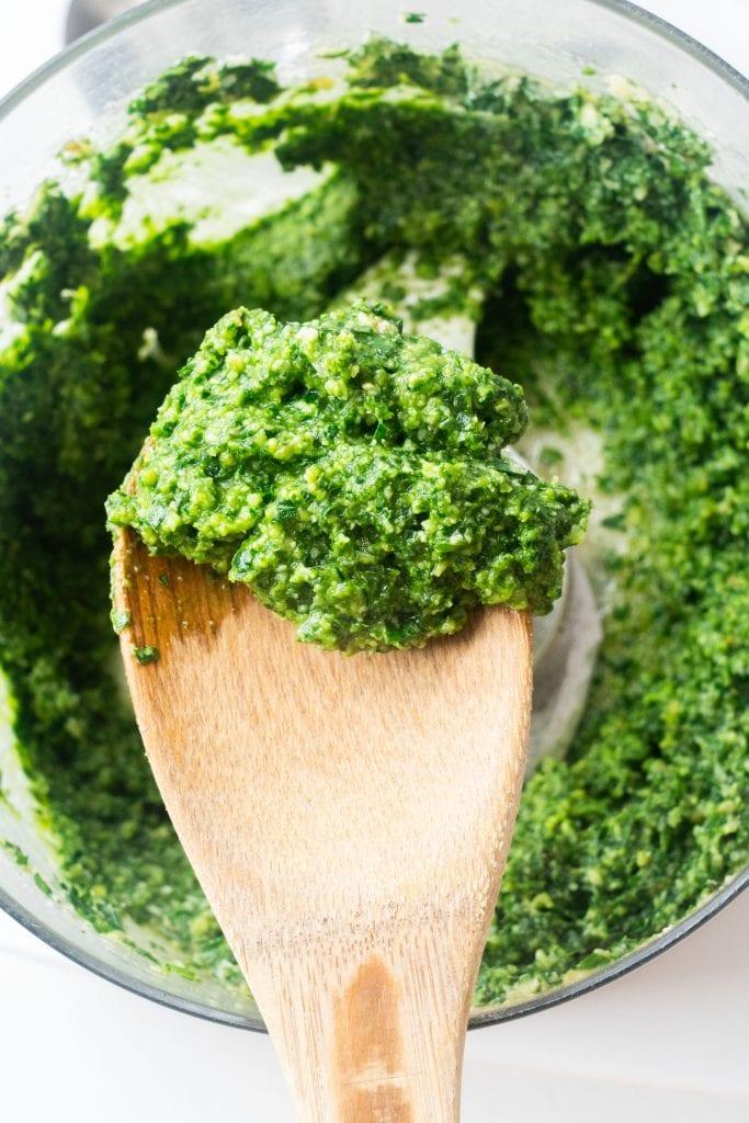 parsley pesto on wooden spoon above food processor.