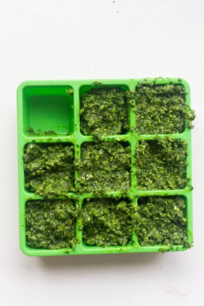 ice cube tray filled with pesto.