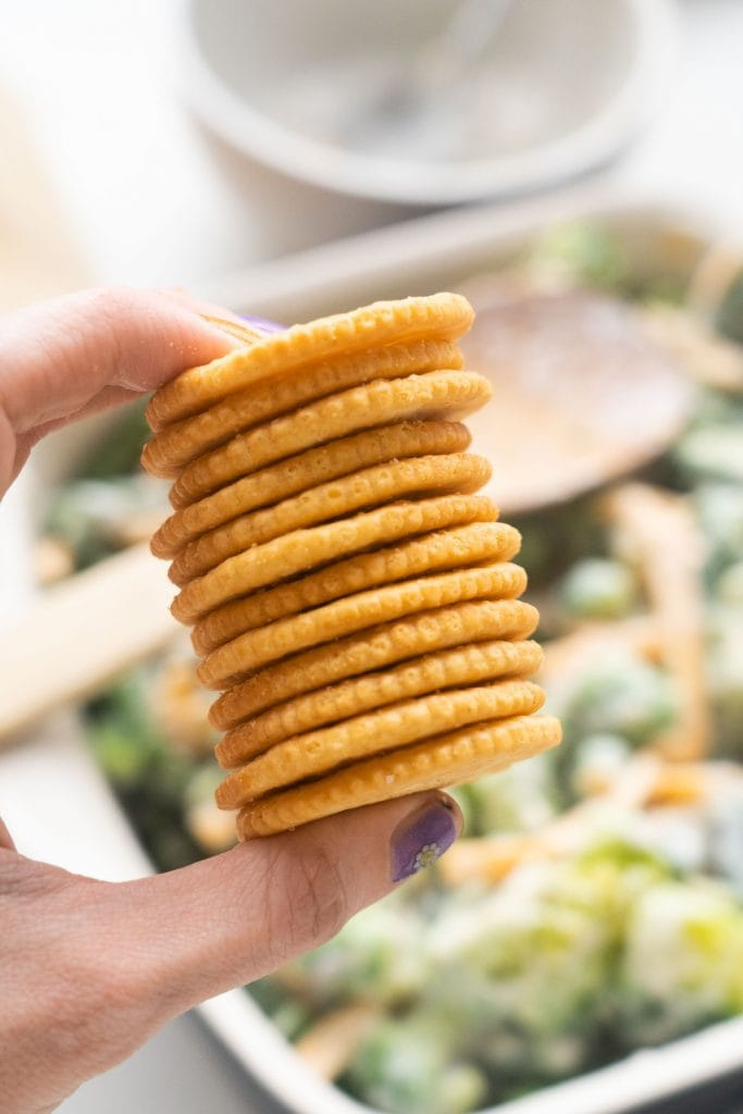 hand holding a stack of ritz crackers.