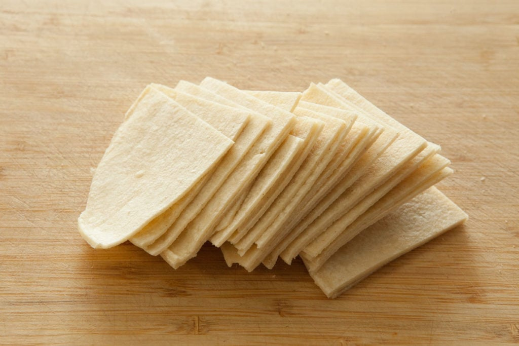 Easy 2 ingredient corn tortilla chips recipe.   This simple homemade recipe will have baked chips made in 10 minutes.  You'll never buy a bag of tortilla chips again!