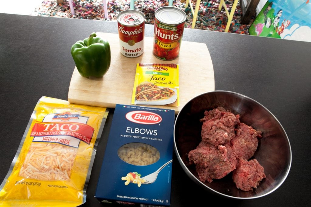 green pepper, tomato soup, diced tomatoes, taco seasoning, cheese, elbow noodles and ground beef on countertop