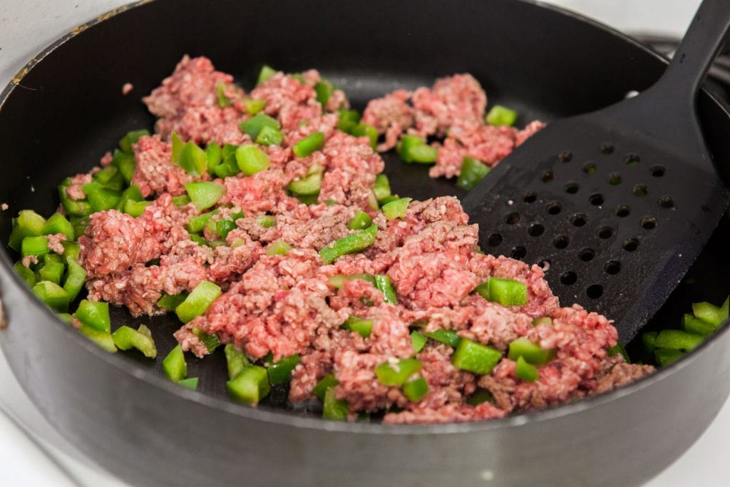 browning ground beef with green pepper in pan