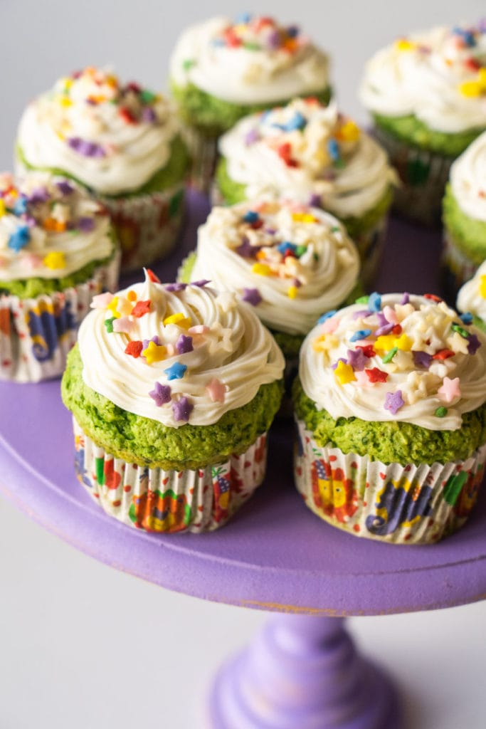 Set of green cupcakes in cupcake liners with sprinkles on top.