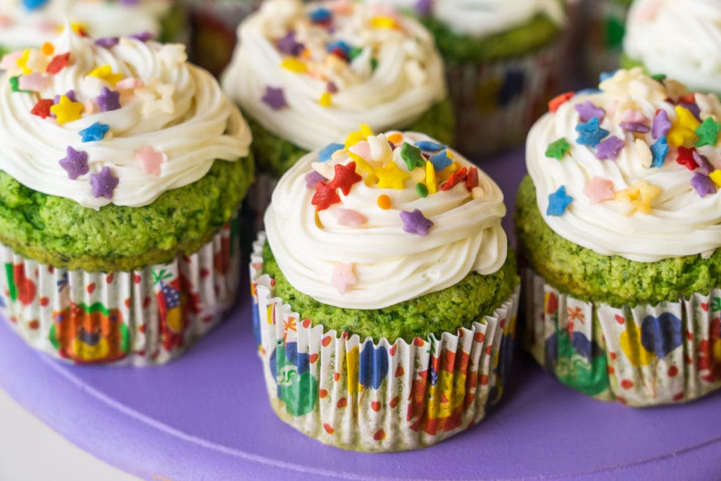 Green cupcakes with white icing and sprinkles