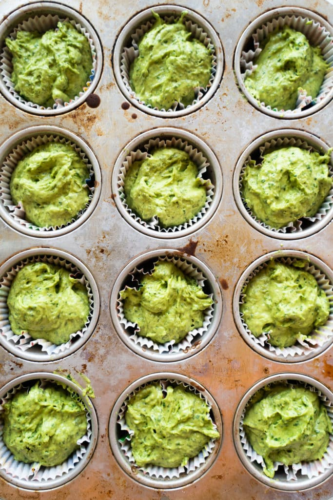 Green cupcake batter in muffin pan.