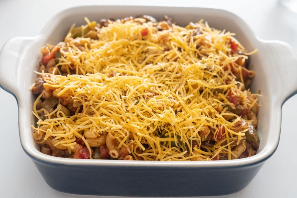 shredded cheddar cheese on top of unbaked casserole in baking dish