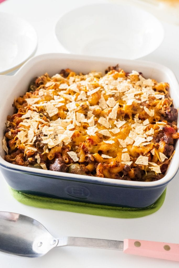 bake taco casserole with tortilla chips on top on white table with white bowls surrounding it