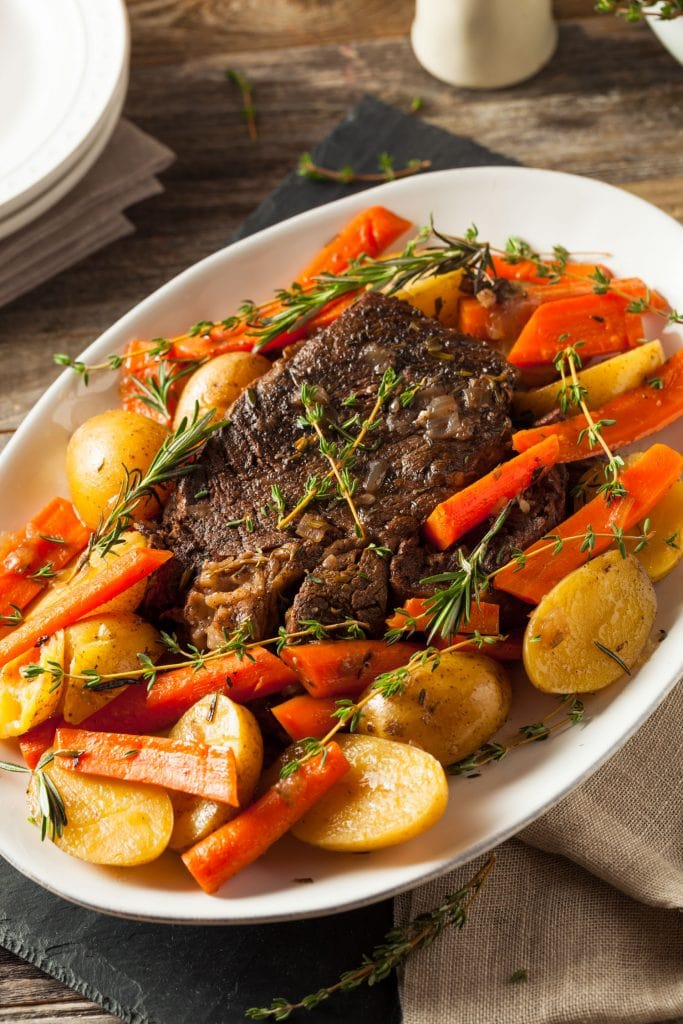 pot roast on white plate being served with potatoes and carrots