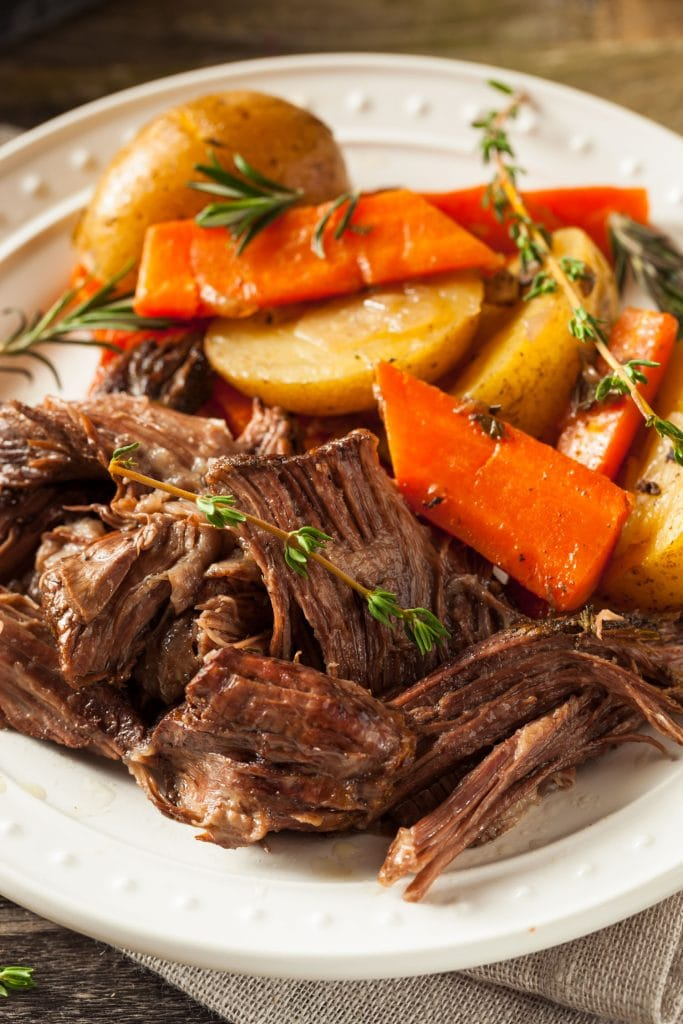 tender pot roast on plate with carrots and potatoes