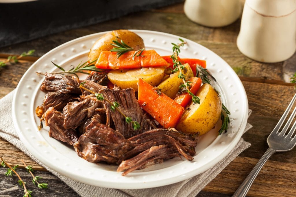 white plate with pot roast, carrots, potatoes, thyme on brown table with fork next to it