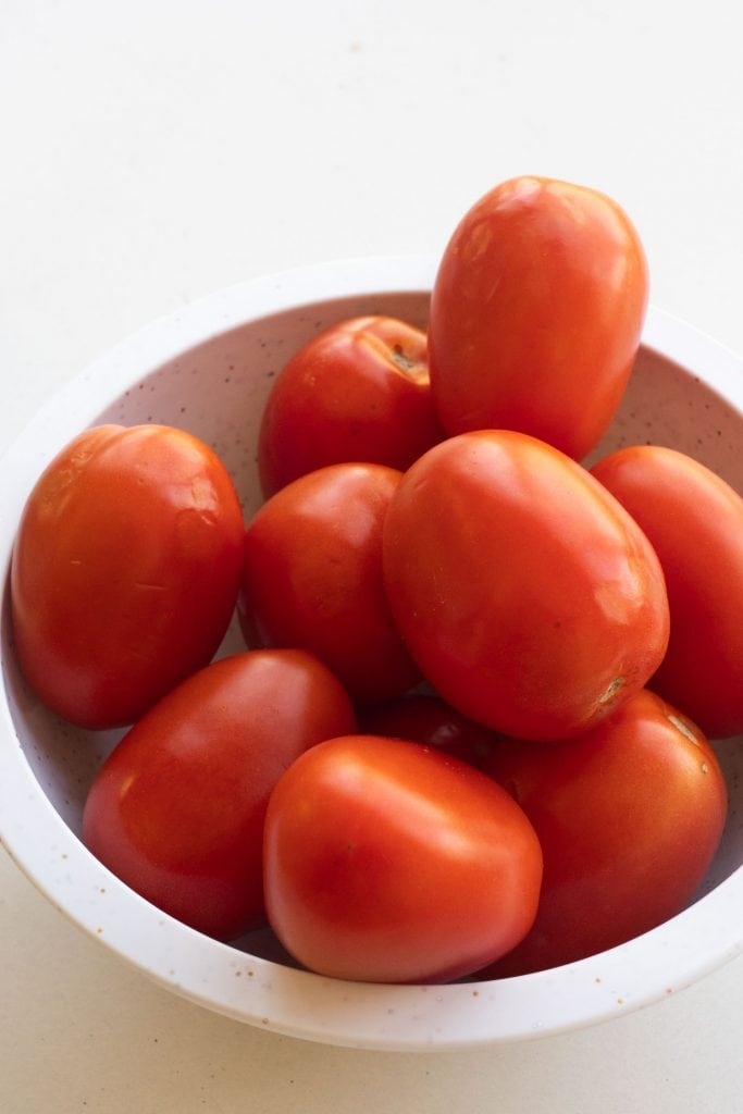 roma tomatoes in white bowl on table.