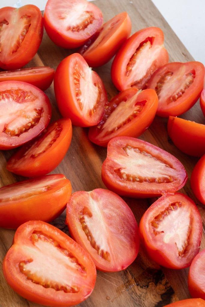 tomatoes cut in half on cutting board
