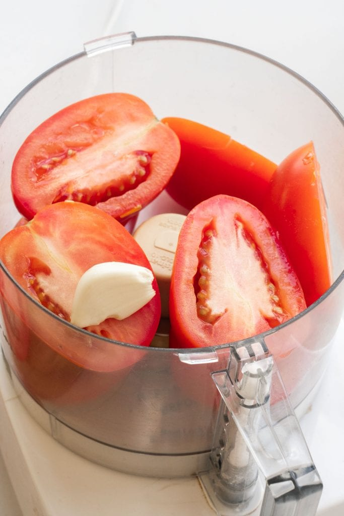 tomatoes and garlic in food processor bowl.