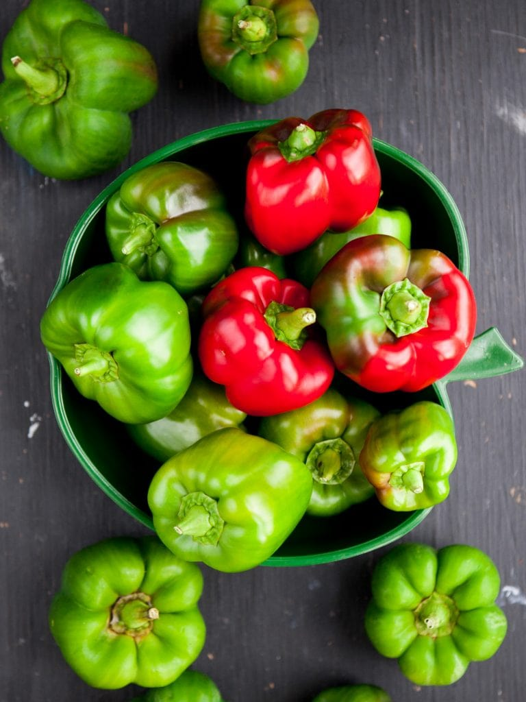 fresh green peppers in dish on table.