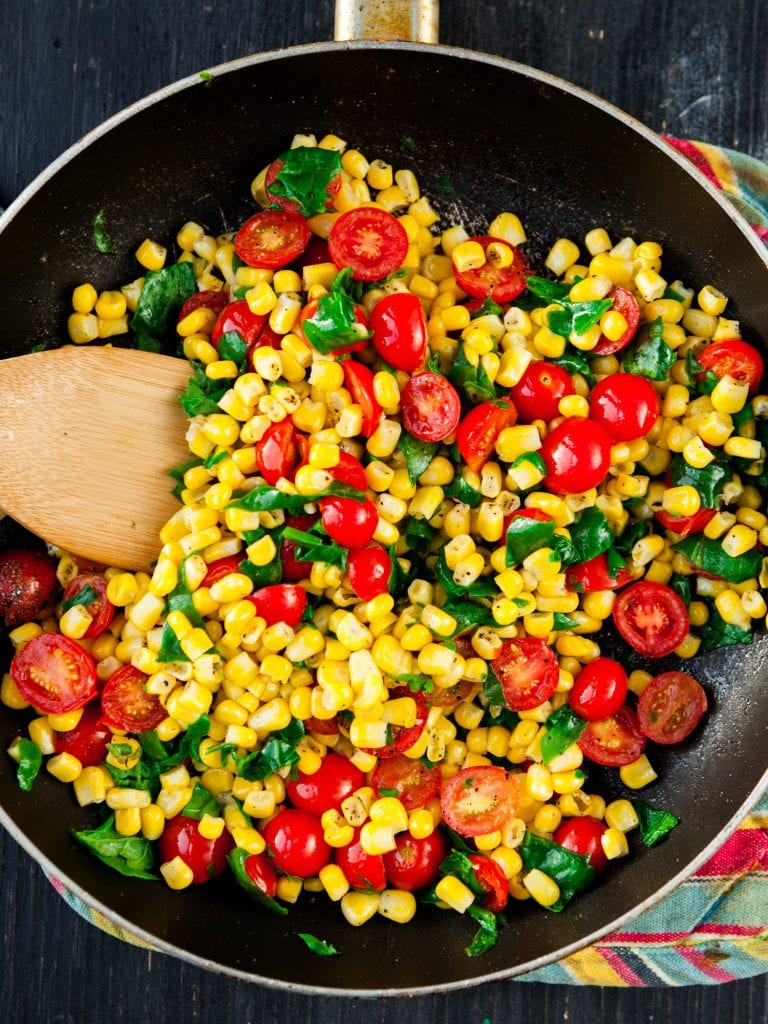 corn, tomatoes and spinach in skillet.