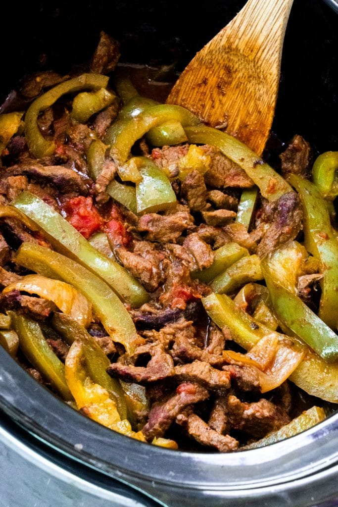 spoon stirring cooked steak and green peppers in crockpot.