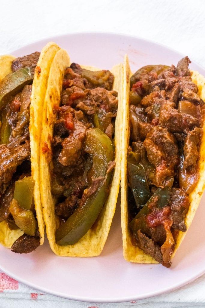 slow cooker steak tacos in hard shells on pink plate.