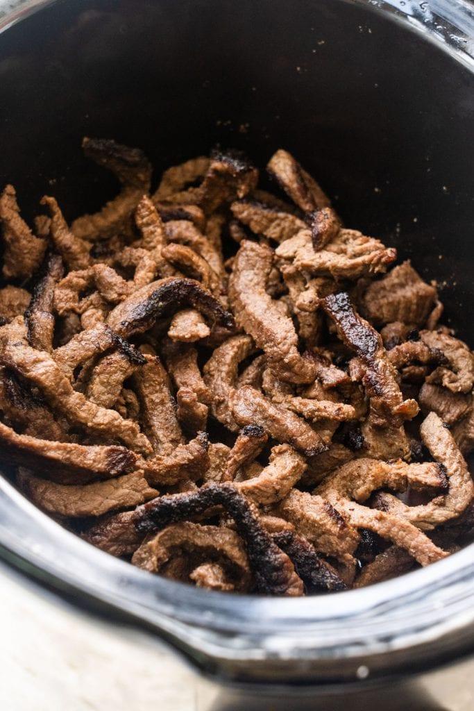 browned rib eye steak in slow cooker.