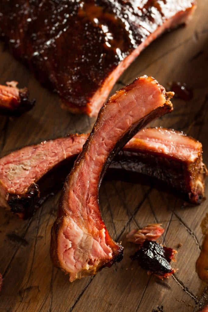 pork spare ribs on top of each other on wooden cutting board
