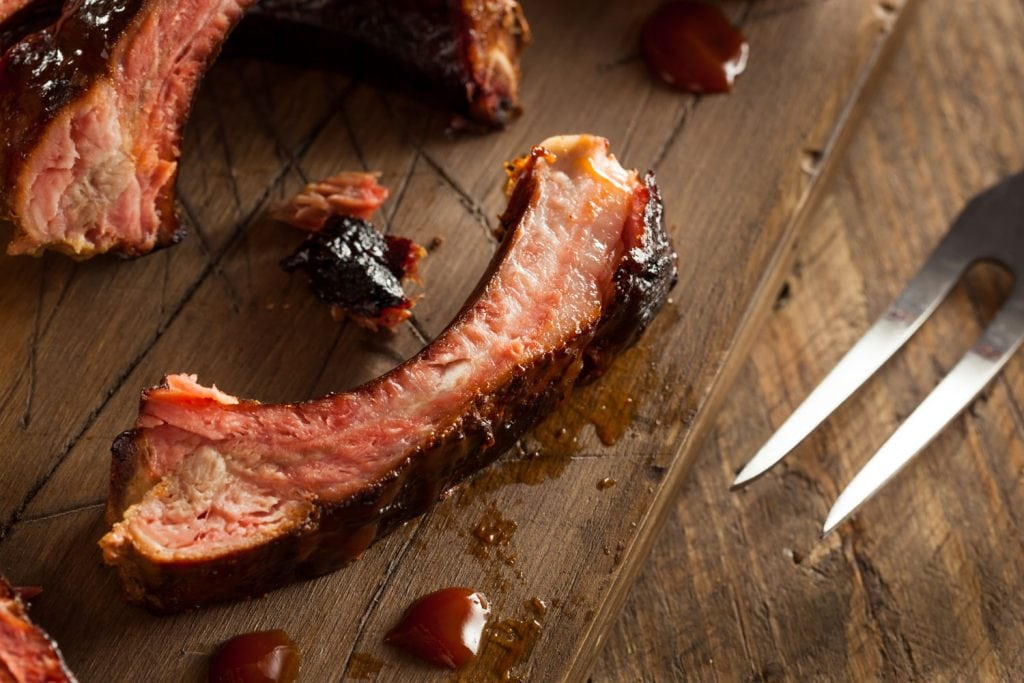 fork next to juicy spare rib on wooden cutting board