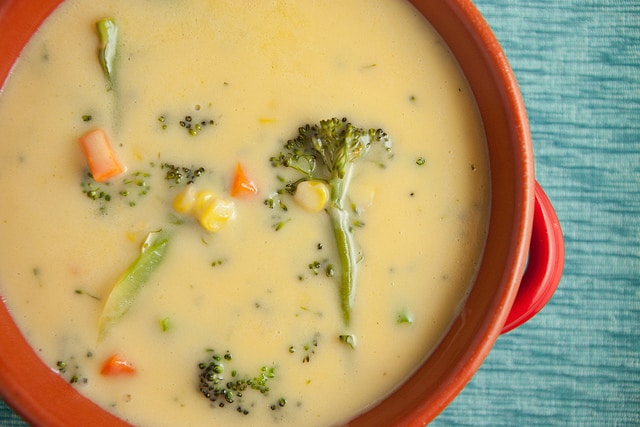 This Creamy Broccoli Cheese Soup recipe is a family favorite! I love serving it as comfort food on a cold night!  This soup is made with broccoli, carrots and Velveeta cheese!