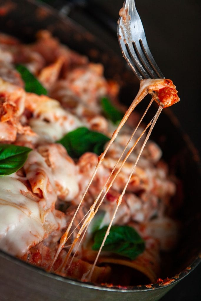 cheese being lifted by fork out of skillet lasagna