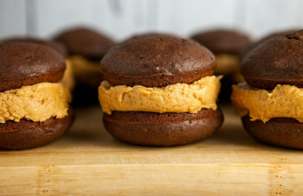 horizontal image of chocolate whoopie pies on cutting board.