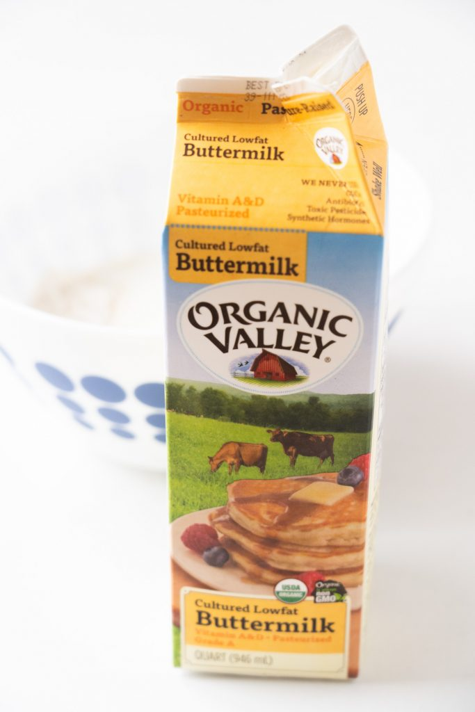 container of buttermilk on table in front of bowl of waffle batter.