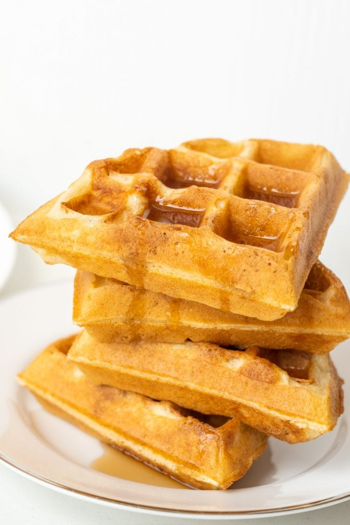 stack of waffles with syrup on them on plate.