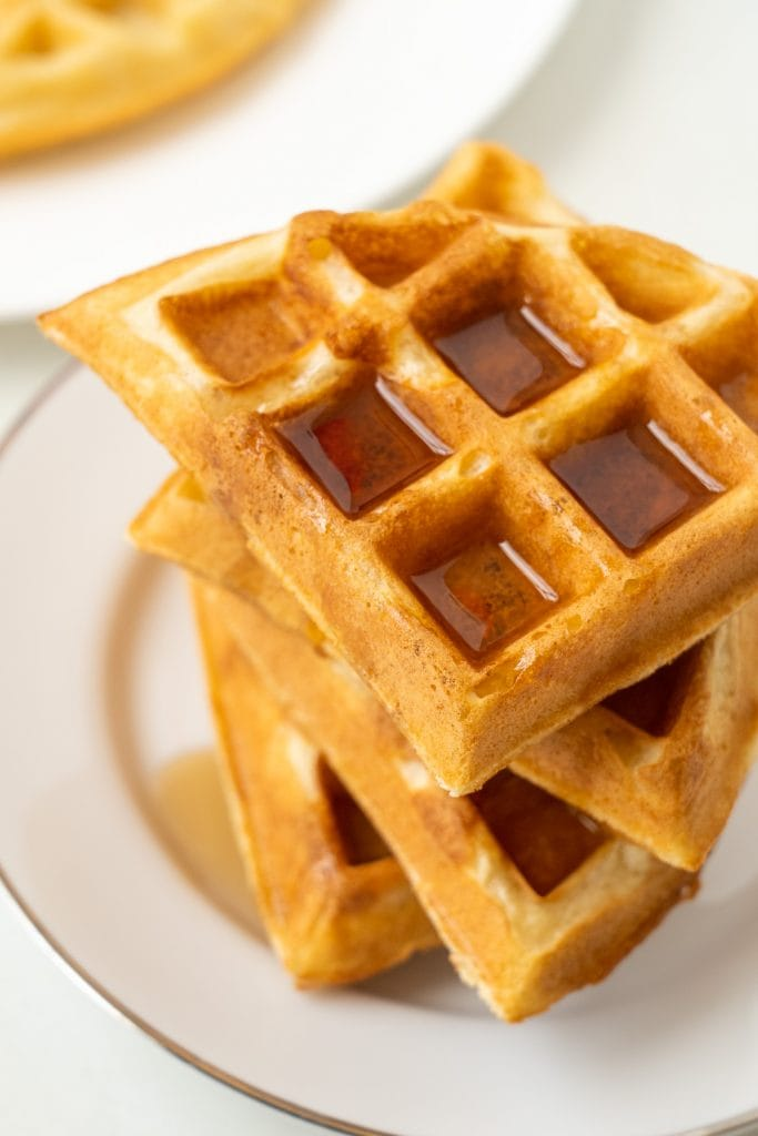 fluffy waffles with syrup on them on white plate.
