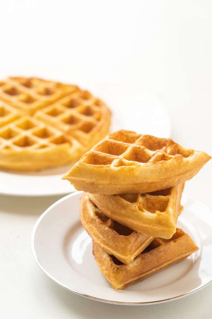 stack of 4 waffle pieces on plate with waffle in background.