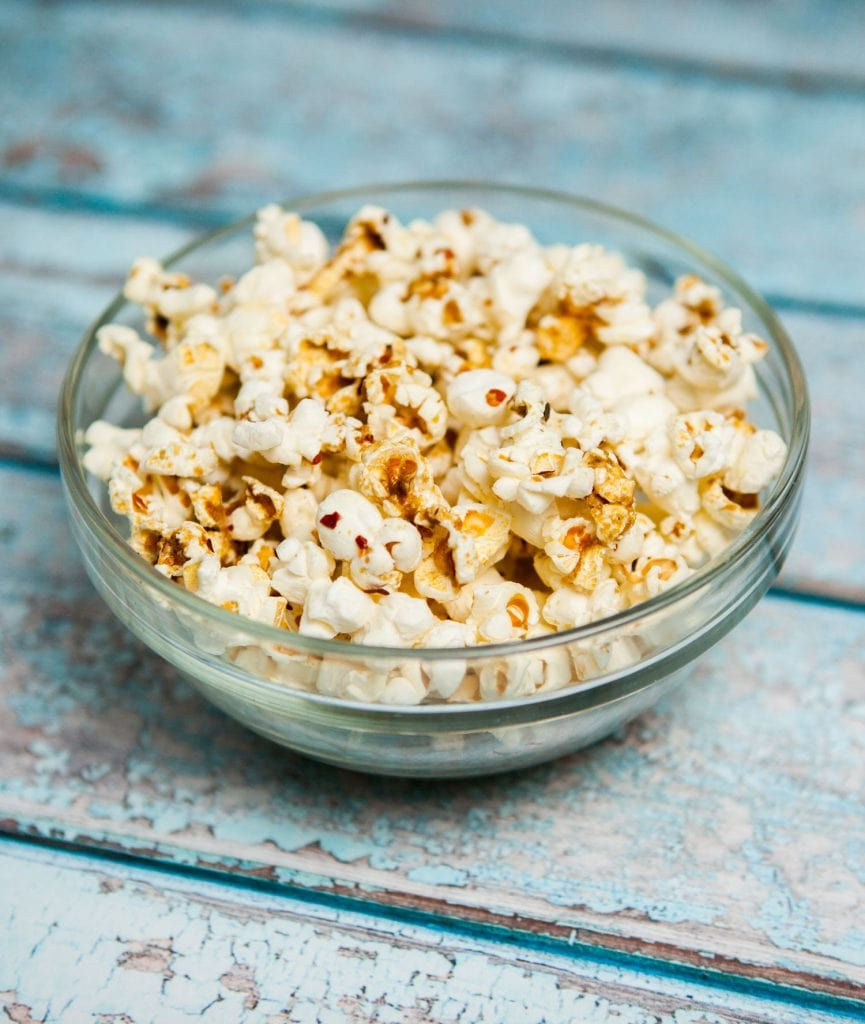 fresh wasabi kettle corn popcorn in bowl on blue table