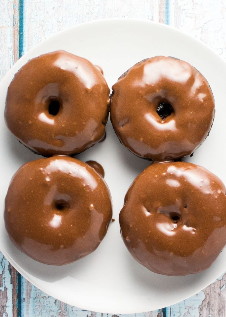 4 chocolate donuts with chocolate frosting on white plate.