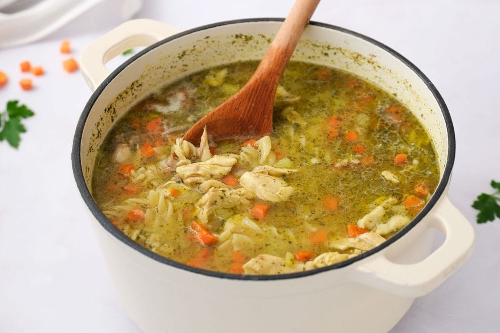 homemade chicken noodle soup with vegetables in soup pot.