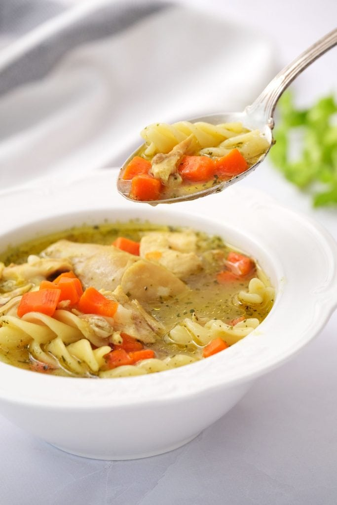 spoon coming out of bowl filled with delicious homemade chicken noodle soup.