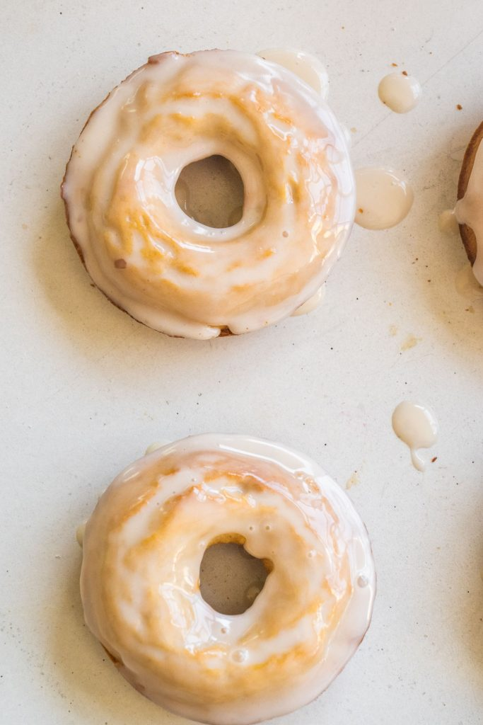 two donuts sitting on white table, glaze drippings on table too.
