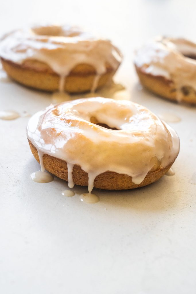 donuts on table with vanilla frosting dripping down sides.