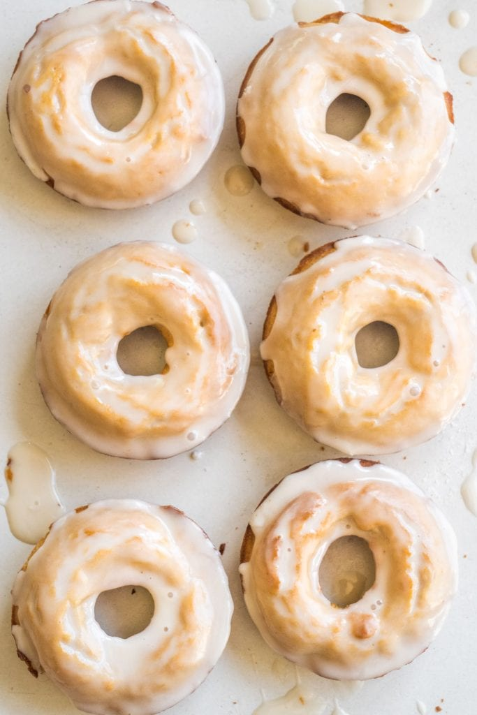 6 peanut butter donuts with white vanilla glaze sitting on white table.