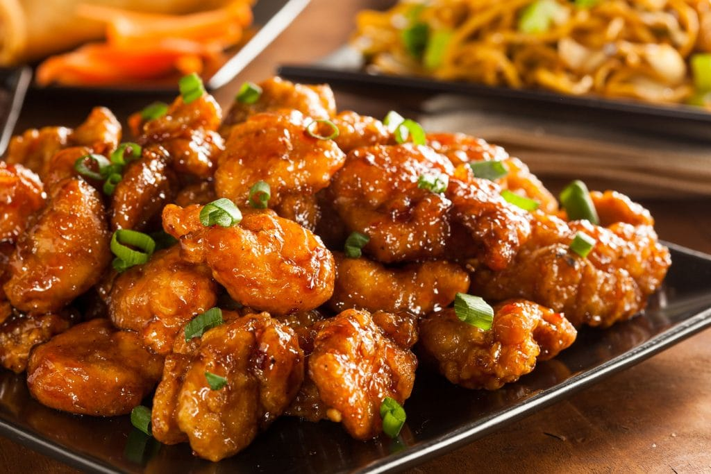 general tsos chicken on black plate with other side dishes in back.