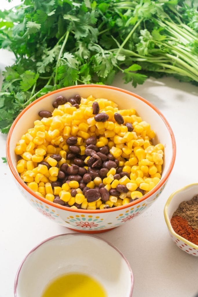 big bowl filled with corn and black beans, olive oil and spices in smaller bowls  around big bowl.