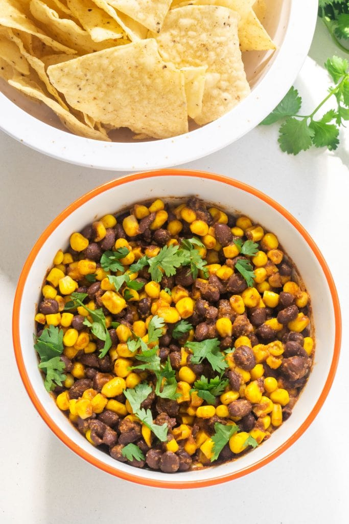 bowl filled with black bean corn salsa with cilantro on top, next to bowl of tortilla chips.