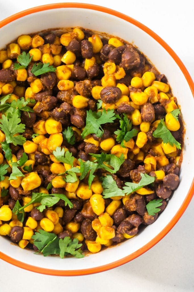 bowl filled with black bean corn salsa with chopped cilantro on top.