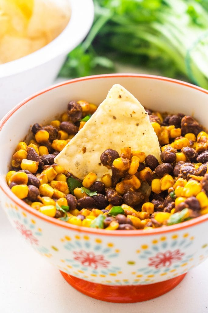 tortilla chip in bowl of black bean corn salsa.