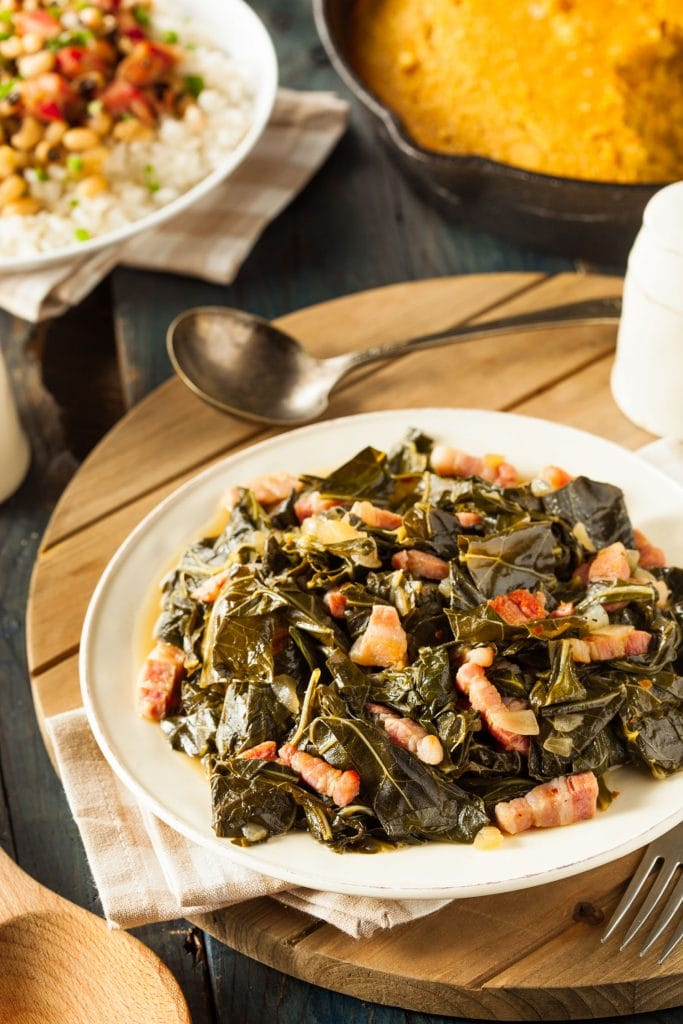 collard greens on plate next to cornbread and black eyed peas on table.