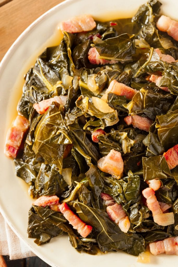 collard greens and salty bacon on white plate on table