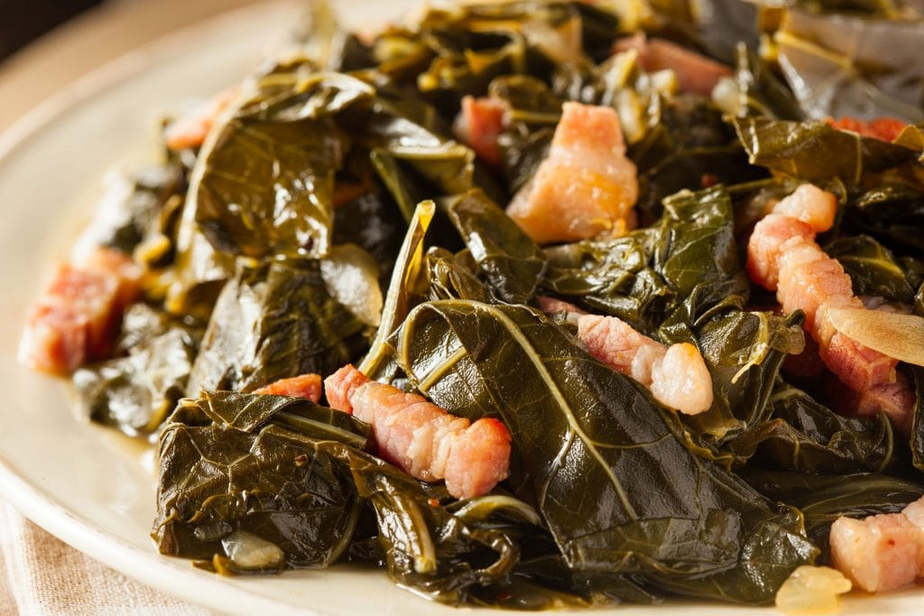 collard greens on serving plate on table with linens.