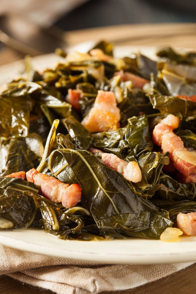 closeup of collard greens and bacon on serving plate.