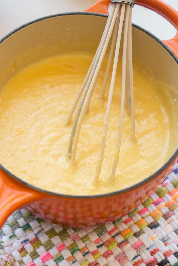saucepan filled with creamy cheese sauce with whisk in it.