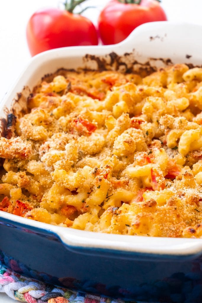 baked macaroni and cheese with tomatoes in blue baking dish.