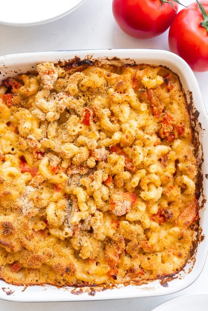 tomato macaroni and cheese with browned top on white table with red tomatoes on side.